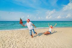 Young couple running at sea beach in santa hats with color sled Royalty Free Stock Image