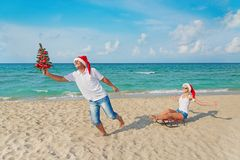 Young couple running at sea beach in santa hats with sled and ch Stock Photo