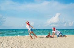 Young couple running at sea beach in santa hats with sled and ch. Young couple running at sea beach in red santa hats with color sled and decorated christmas Stock Image