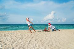 Young couple running at sea beach in santa hats with sled and ch Stock Photography