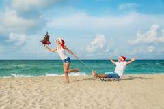 Young couple running at sea beach in santa hats with sled and ch. Young couple running at sea beach in red santa hats with color sled and decorated christmas Royalty Free Stock Image