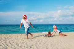 Young couple running at sea beach in santa hats with sled and ch Royalty Free Stock Photos