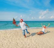 Young couple running at sea beach in santa hats with sled and christmas tree Stock Photo