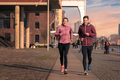 Young couple running on a seafront promenade Royalty Free Stock Photos