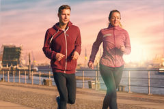 Young couple running on a seafront promenade. Fit active young couple running on a seafront promenade with the athletic women leading the way approaching the stock images