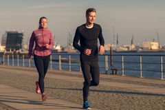 Young couple running on a seafront promenade Stock Photos