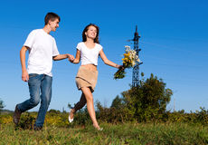 Young couple running on summer meadow Stock Photos