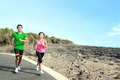 Young couple running together on jogging track. Sporty asian young couple running outside together on jogging track Royalty Free Stock Photos