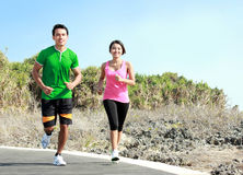 Young couple running together on jogging track. Sporty asian young couple running outside together on jogging track royalty free stock images