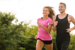 Young couple running together outdoors Stock Images