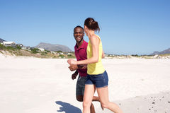 Young couple running together on seashore Stock Photography