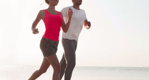 Young couple running together beside the water at the beach. Man Stock Photography