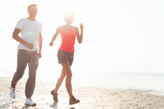 Young couple running together beside the water at the beach. Man Royalty Free Stock Photography