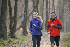 Young Couple Running on the Trail in the Wild Forest Stock Photography