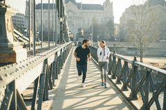 Young couple running in urban enviroment royalty free stock images