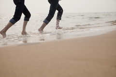 Young Couple Running in the Waves Royalty Free Stock Image