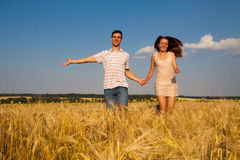 Young couple running through  wheat field Royalty Free Stock Images