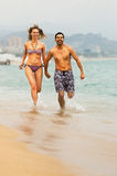 Young couple runs near the sea Stock Images