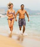 Young couple runs near the sea. Young happy couple runs at sandy beach near the sea royalty free stock photos