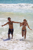 Young couple runs out of the ocean Royalty Free Stock Image