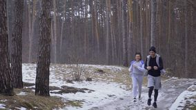 Young couple runs on slippery road in the forest. Young sport people makes morning exercises outdoors. Pretty woman and handsome man wearing sportswear runs in stock video footage