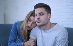 Young couple 20s with man sad and depressed suffering pain maybe broken heart and girlfriend giving her boyfriend support help and. Young couple 20s sitting at royalty free stock image