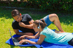 Young couple s using a laptop and headphones Royalty Free Stock Photography