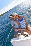 Young couple at sailboat wheel in caribbean sea Royalty Free Stock Photography