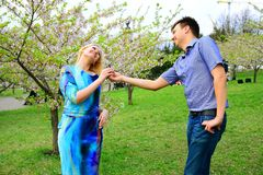 Young couple in the sakura's garden in park Royalty Free Stock Images