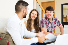 Young couple and salesman talking. Cheerfully about purchase at home stock images