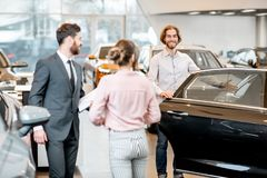 Couple choosing a new car in the showroom. Young couple with salesperson choosing a new car looking on the back seats in the showroom stock photo