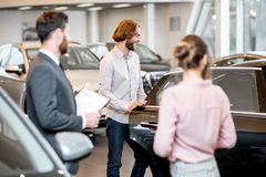 Couple choosing a new car in the showroom. Young couple with salesperson choosing a new car looking on the back seats in the showroom stock photography