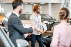 Couple choosing a new car in the showroom. Young couple with salesperson choosing a new car looking on the back seats in the showroom royalty free stock photography