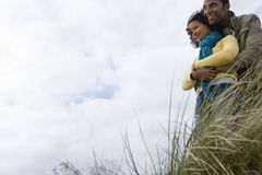 Young couple on sand dune, man embracing woman, low angle view Royalty Free Stock Photos