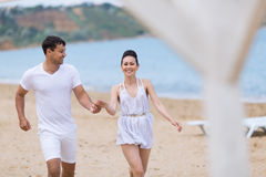 Young couple on sand seashore in cloudy day Royalty Free Stock Image