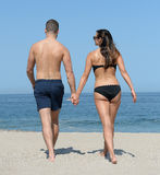 Young couple on sandy beach Stock Images