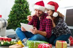 Young couple with Santa Claus hats shopping online Christmas gif Stock Photos