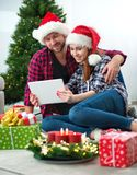 Young couple with Santa Claus hats shopping online Christmas gif Stock Photography