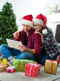 Young couple with Santa Claus hats shopping online Christmas gif Royalty Free Stock Photos
