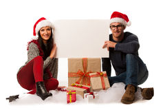 Young couple in santa hat holding blank board for advertisement,. Sitting on the floors in bunch of gifts. Gently smiling and inviting to christmas activities Royalty Free Stock Images
