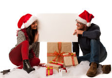 Young couple in santa hat holding blank board for advertisement, Stock Images