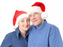 Young couple in santa hats Royalty Free Stock Photos