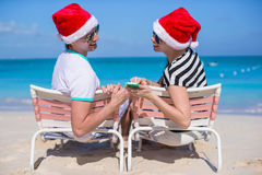Young couple in Santa hats enjoy beach vacation Royalty Free Stock Image