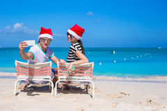 Young couple in Santa hats enjoy beach vacation Stock Image