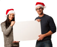 Young couple in santa hats holding blank board for advertisement Stock Photography