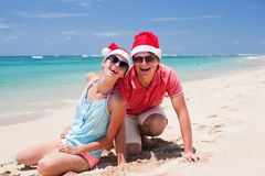 Young couple in santa hats laughing on tropical Royalty Free Stock Image