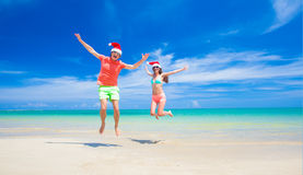 Young couple in santa hats laughing on tropical Royalty Free Stock Images