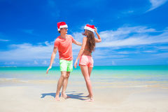 Young couple in santa hats laughing on tropical Stock Photography
