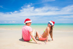 Young couple in santa hats laughing on tropical Royalty Free Stock Photography