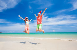Young couple in santa hats laughing on tropical Stock Photos